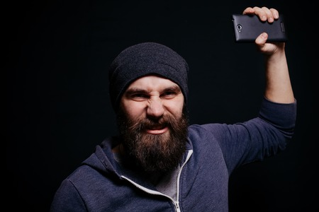 narcissist: Beautiful young man with a beard in a gray hoodie makes self, smiling, studio shot on black background, aggressive guy throws the phone