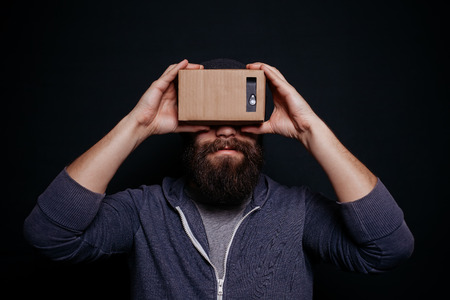 card board: Color shot of a young man looking through a card board, a device with which one can experience virtual reality on a mobile phone.