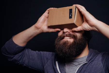 which one: Color shot of a young man looking through a card board, a device with which one can experience virtual reality on a mobile phone. guy smiling