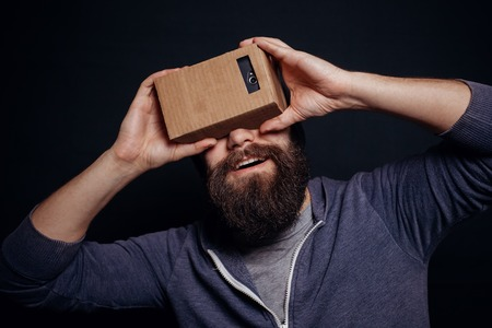 card board: Color shot of a young man looking through a card board, a device with which one can experience virtual reality on a mobile phone. guy smiling