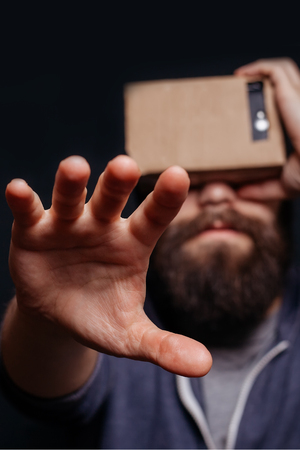 card board: Color shot of a young man looking through a card board, a device with which one can experience virtual reality on a mobile phone. man touches the hand. blurry photos