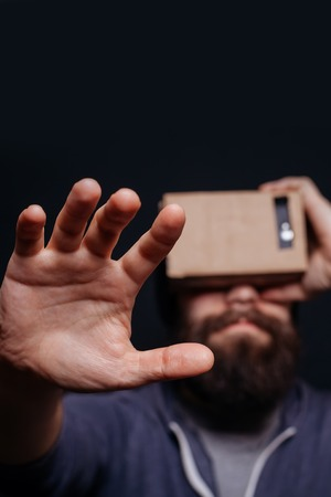 which one: Color shot of a young man looking through a card board, a device with which one can experience virtual reality on a mobile phone. man touches the hand. blurry photos