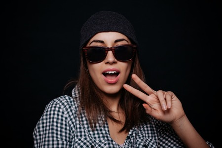 arrogant teen: Hipster teenage girl with beanie hat and plaid shirt posing making confident facial expression, smiling, showing two fingers against the black wall background. Modern young people. Stock Photo