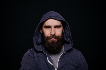 looking directly at camera: Handsome male big beard in hoodies, studio shot on black background, looking directly at the camera