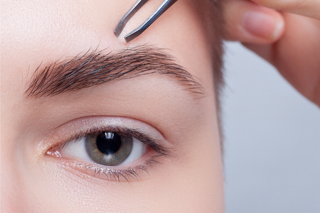 Young woman with short hair plucking eyebrows with tweezers close up, studio shot. on a light background. beauty shot .Closeup part of face, woman plucking eyebrows depilating with tweezers.