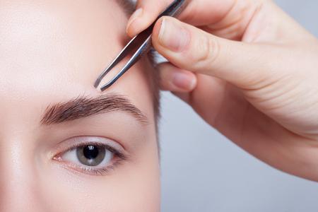 bald: La mujer joven con el pelo corto depilarse las cejas con pinzas de cerca, tiro del estudio. sobre un fondo claro. de belleza saltó .closeup parte de la cara, mujer depilarse las cejas depilación con pinzas. Foto de archivo