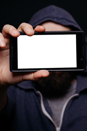 cool gadget: Hipster man with a beard taking picture smartphone self-portrait, screen view, snapshot studio on a black background, Phone white screen Stock Photo