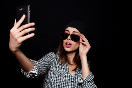 Hipster kühlen Mädchen auf dem Smartphone Selbstporträt, Snapshot-Studio auf einem schwarzen Hintergrund, die Foto