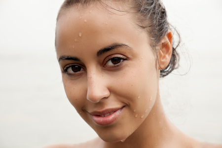 female in douche: Face of beautiful girl with water on the skin. Youth and Skin Care Concept. Make up and Hair. Close up, selected focus. Stock Photo