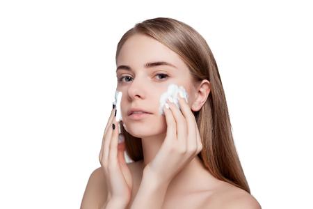 mujer bañandose: Hermosa mujer de limpieza de su cara con un tratamiento de espuma en un fondo de luz blanca. Retrato de belleza. Mujer hermosa del balneario sonriente. Piel fresca perfecta. Pura belleza del modelo. Juventud y Cuidado de la piel Concept
