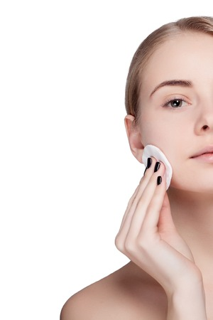 Woman using cotton pad. Happy smiling beautiful young woman cleaning skin by cotton pad. light background. Beautiful Spa Woman Smiling. Perfect Fresh Skin. Youth and Skin Care Concept Standard-Bild