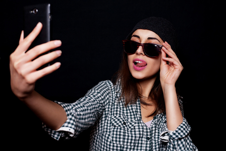 close-up portrait of young beautiful slim sexy young brunette woman on black background in studio wearing sunglasses and hat smiling and posing selfi doing on your phone