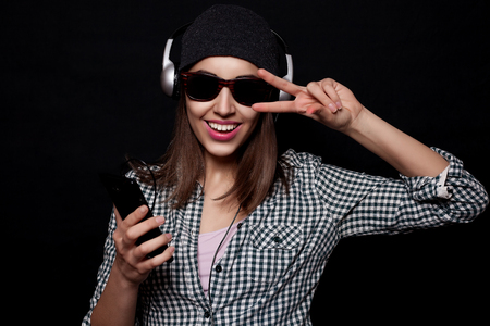 knit cap: beautiful girl happy listening to music with big headphones with a phone or player, knit cap, photo studio, portrait of a woman on black background