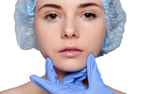 surgeons hat: Beauty Woman face surgery close up portrait. Female model. studio shot beauty on a white background, Plastic surgery touching the head of a female face blue medical gloves