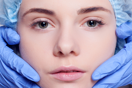 surgeons hat: Beauty Woman face surgery close up portrait. Female model. studio shot beauty octor in the background, Plastic surgery touching the head of a female face blue medical gloves Stock Photo