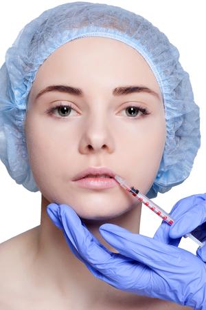 inyeccion: Mujer joven atractiva que consigue la inyección de cosmética, una inyección en el labio superior, sobre fondo blanco. Doctores manos haciendo una inyección en la cara, primer plano. Tratamiento de belleza.