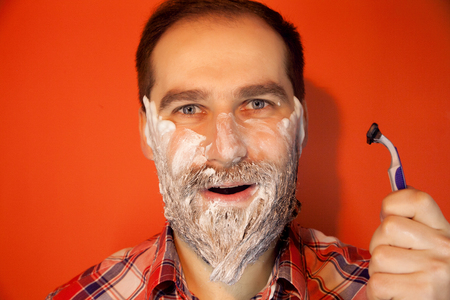 color photo: Handsome man with shaving foam on his face and razor, smiling, happy on a red background, color photo