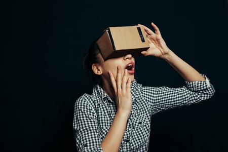 carton: Disparo de color de una mujer joven que busca a través de un cartón, un dispositivo con el que uno puede experimentar la realidad virtual en un teléfono móvil.