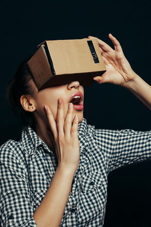 which one: Color shot of a young woman looking through a cardboard, a device with which one can experience virtual reality on a mobile phone. Stock Photo