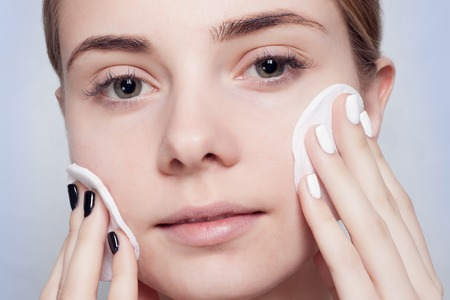 Femme à l'aide de coton. Heureuse souriante belle jeune femme nettoyant la peau par un tampon de coton. fond clair.