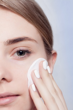 removing make up: Woman using cotton pad. Happy smiling beautiful young woman cleaning skin by cotton pad. light background.