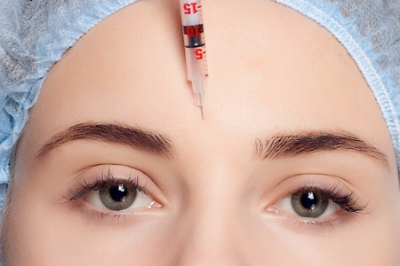 face shot: Botox injection. Attractive young woman in medical headwear and sketches on face keeping eyes closed while doctors hand making an injection in face