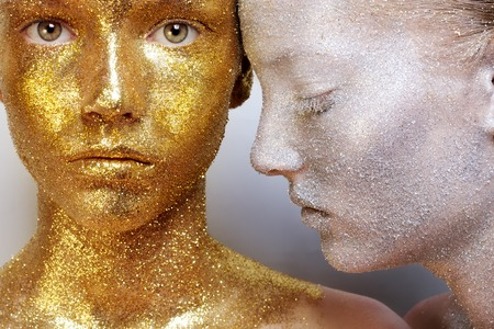 unreal: Beautiful, amazing portrait of two woman. Unreal make up like a space. Closeup shooting in studio with silver background. Emotion, posing of model. gold silver glitter.