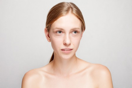 Beautiful Face of Young Woman with Clean Fresh Skin close up isolated on white. Beauty Portrait. Beautiful Spa Woman Smiling. Perfect Fresh Skin. Youth and Skin Care Concept. dark circles under eyes Standard-Bild