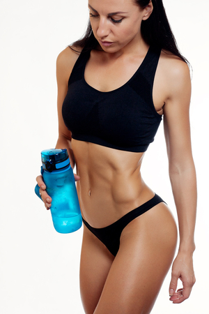 Front view of slim fitness woman drinking water. Full body length portrait isolated over white background.