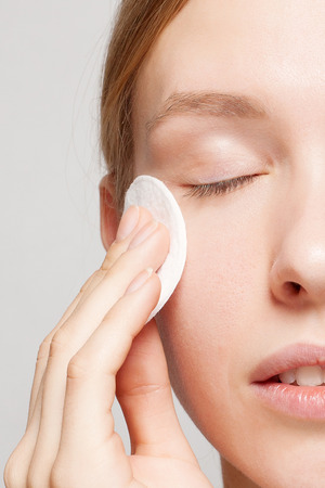A picture of a happy woman cleaning her face with cotton pads over white background. Beautiful Face of Young Woman with Clean Fresh Skin close up. Beauty Portrait. Youth and Skin Care Concept Stock Photo