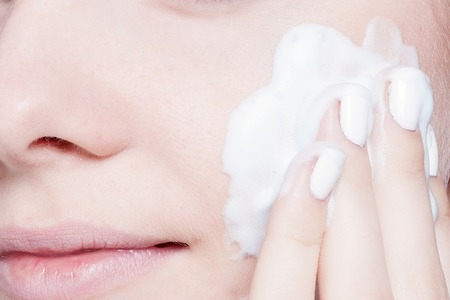 Close-up woman clears skin foam on a gray background