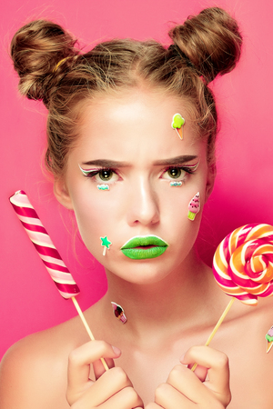 broadly: Beautiful young woman holds in hands candy smiling broadly. Stylish girl with bright makeup and candy in her hands, isolated on pink background Stock Photo