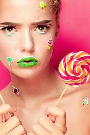 keep an eye on: Beautiful young woman holds in hands candy smiling broadly. Stylish girl with bright makeup and candy in her hands, isolated on pink background Stock Photo