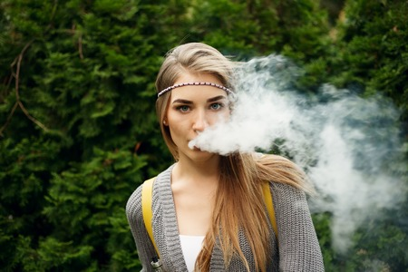 Happy vaping young white blonde girl.Smiling female model smoking fruit flavored e-liquid or e-juice with vaporizer device or e-cig.Modern gadget for smokers 免版税图像