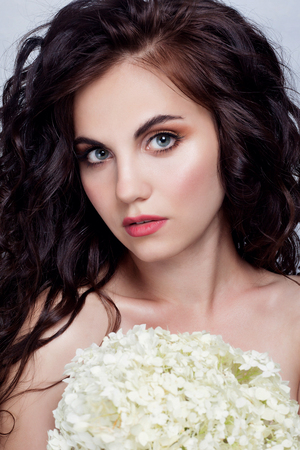perming: Beautiful girl with long wavy and shiny hair . Brunette woman with curly hairstyle