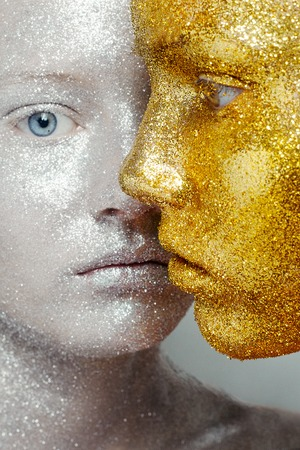 Beautiful, amazing portrait of two woman. Unreal make up like a space. Closeup shooting in studio with silver background. Emotion, posing of model. gold silver glitter.