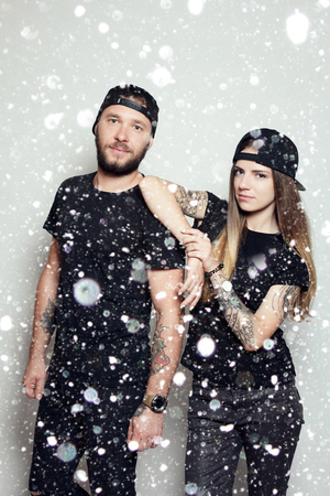 christmas tattoo: winter, christmas, people, happy concept- fashion beautiful couple together. Tattoo Hipster boy and girl. Bearded young man and blonde over snow background