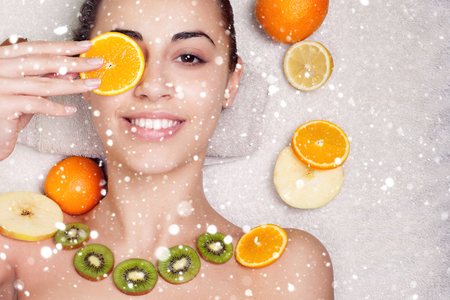 winter, christmas, people, beauty, concept- Natural homemade fruit facial masks. Fresh fruit over snow background