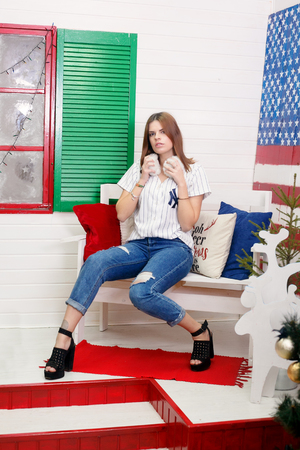 winter, christmas, people, beauty concept- Beautiful, sexy, young brunette woman in style cloth posing with national usa flag in background. 4th july concept.