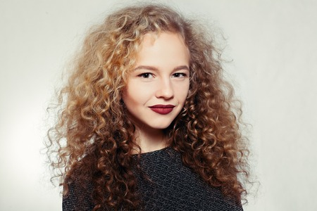 people, youth and beauty concept - Beauty young woman with curly big and long hair. Permed hair. Glamour lady, Beauty Girl on grey background. Beautiful Woman Portrait. Blond Wavy Hair