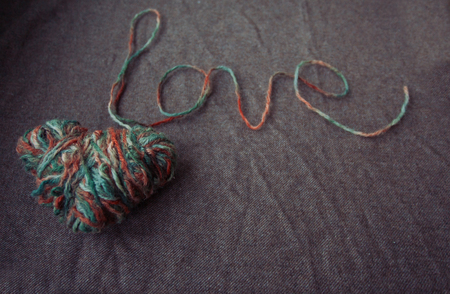 st valentin: holidays, love and valentines day concept - The word love written of wool yarn on a brown background. Valentines Day background Stock Photo