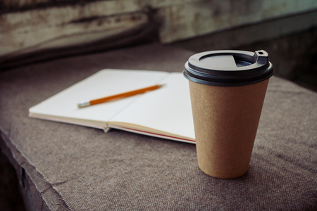 business, lifestyle, food and coffee concept -Pencil, notebook and paper coffee cup on a brown fabric background