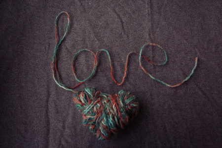 holidays, love and valentines day concept - The word love written of wool yarn on a brown background. Valentines Day background Stock Photo