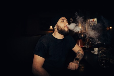 technologies, people, food and lifestyle concept - handsome young bearded man holds an electronic cigarette, e-cig and exhaling a cloud of vapor. guy vaping in sunglasses with tattoos