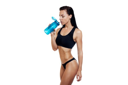 health, people, Sport and lifestyle concept - Front view Fitness woman happy smiling holding water bottle. Healthy lifestyle photo. portrait isolated over white background. Stock Photo