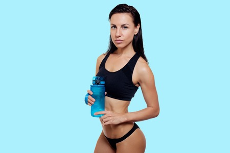 health, people, Sport and lifestyle concept - Front view Fitness woman happy smiling holding water bottle. Healthy lifestyle photo. portrait isolated over blue background.