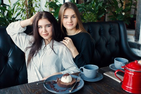 conversating: technologies, lifestyle, food, people, teens and coffee concept - Two young women taking selfie with smart phone in the city center. Happiness concept about people and drink tea