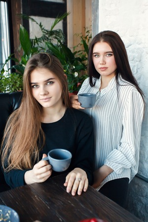 conversating: technologies, lifestyle, food, people, teens and coffee concept - Two young women taking selfie with smart phone in the city center. Happiness concept about people , drink tea Stock Photo