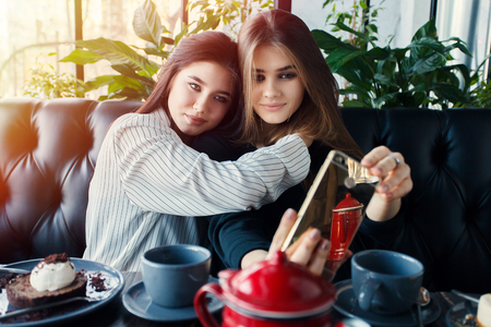 conversating: Two young women taking selfie with smart phone Stock Photo