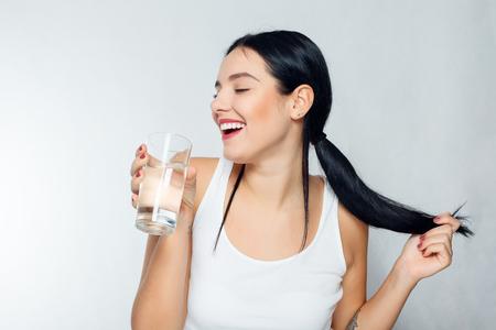 健康、人々、食べ物、スポーツ、ライフ スタイル、美容コンテンツ - 水のガラスでの若い女性の笑顔